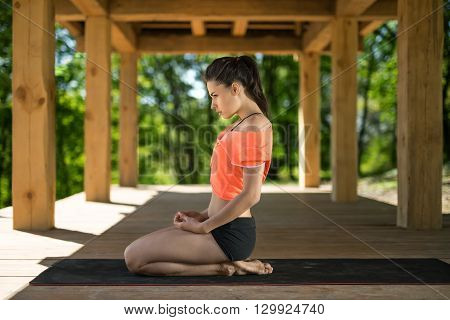 Attractive girl sits sideways on her heels on the black yoga mat on the wooden terrace on the nature background. She holds her hands on her legs. She looks in front of herself with omitted chin. She wears black shorts and orange t-shirt. Outdoors. Horizon