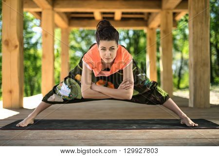 Amazing girl makes wide-legged forward bend on the black yoga mat on the wooden terrace on the nature background. She holds her crossed arms under her torso. She looks into the camera with a smile. She wears orange t-shirt and the wide olive pants with im