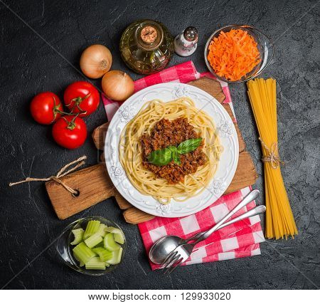 Spaghetti bolognese with ingredients on black background. Top view with copy space.