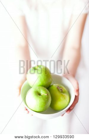 Young child is giving or receiving a bowl with apples.