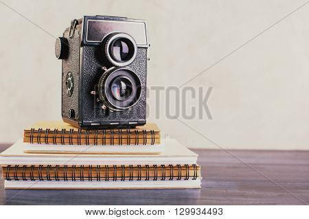 Closeup of wooden table with retro camera placed on notepad stack