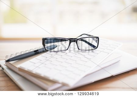 Closeup of glasses keypad pen notepads and laptop