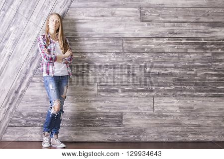 Casually dressed young woman with something on her mind standing against wooden plank wall. Mock up