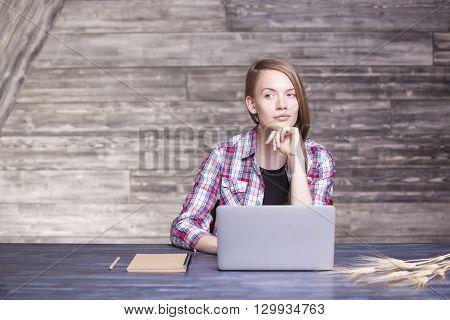 Thoughtful female in casual shirt and with pencil in hand sitting at wooden desk with laptop notepad and wheat spikes