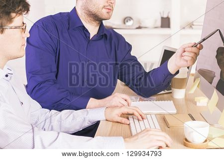 Businessmen in office looking at blank computer display and discussing something