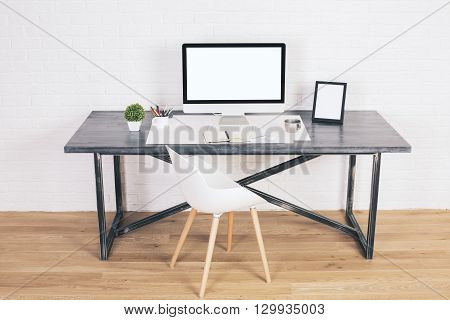 Designer desk with blank white computer screen picture frame and chair next to it on wooden floor and brick background. Mock up
