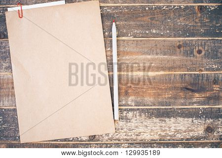 Top view of blank brown paper and pencil on aged wooden desktop. Mock up