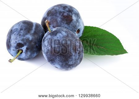 Organic plums fruit with leaf on white. Closeup.