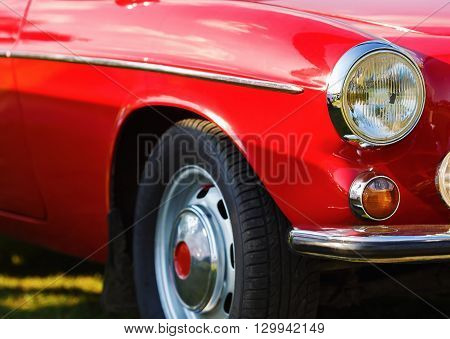 Red vintage car. Close-up fragment of the red vintage car. Headlight of vintage red car. Retro car. Selective focus.