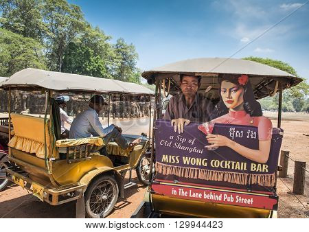 Siem Reap, Cambodia - MAY 04, 2016: Tuk-tuk driver waits for customers. Tuk-tuks are the most common and popular way to get around Siem Reap.