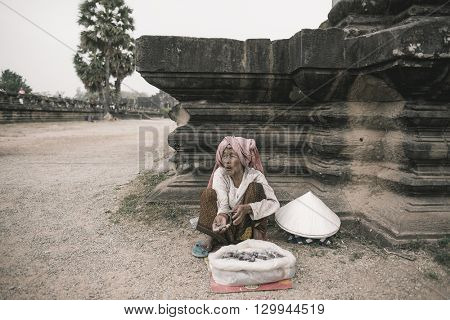 Siem Reap, Cambodia - MAY 04, 2016: The impoverished old woman begs in the courtyard of a Buddhist temple