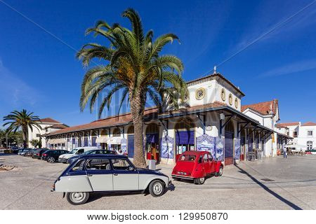 Santarem, Portugal. September 10, 2015: The Farmers Market of Santarem with two classic European cars, the Citroen Dyane (gray) and the Citroen 2cv (red) parked in front of it.