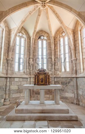 Santarem, Portugal. September 11, 2015: The aisle, altar and a gilded baroque tabernacle in the medieval church of Santa Cruz. 13th century Gothic Architecture. Santarem, Portugal.