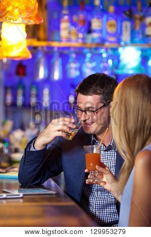 Handsome man enjoying drinks with a female companion in a brightly colored nightclub interior seated at a table together
