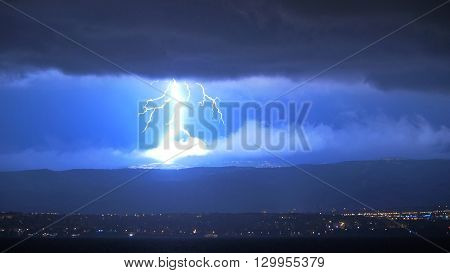 Panoramic Scenic of Dramatic and Forceful Lightening Striking Hills Above Town at Night, Lighting Up Sky with Storm Clouds