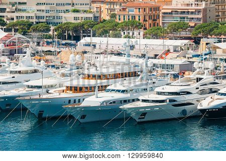 Monte Carlo, Monaco - June 28, 2015: White Yachts Of Different Sizes Are Moored At City Pier, Jetty In Sunny Summer Day