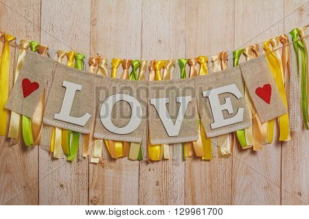 Love White Wedding Letters Hanging Sign With Ribbons On Light Wooden Background