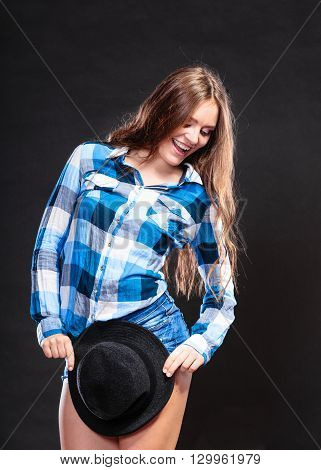 Portrait of pretty gorgeous woman. Attractive young girl with long hair wearing checked shirt and jeans shorts holding hat. Country style fashion.