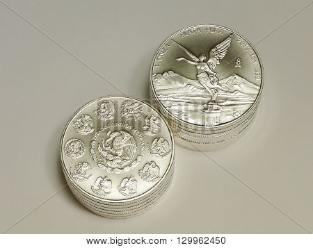 Two stacks of 1 ounce Mexican Silver Libertad coins on grey background.