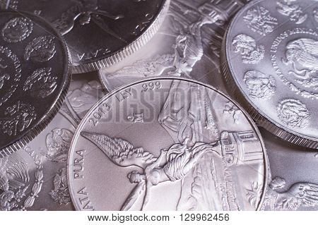 Close up shot of a pile of 1oz Mexican Silver Libertad coins.