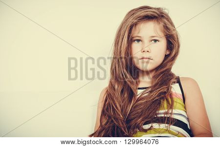 Portrait of sad unhappy little girl kid. Lonely depressed child. Bad mood.