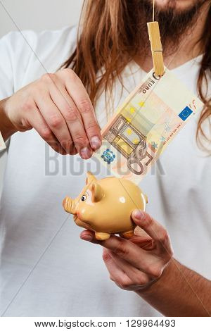 Spending money concept. Male hands with piggybank and euro banknote cash. Savings.