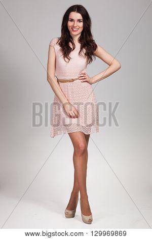 Young cute woman posing in beige dress