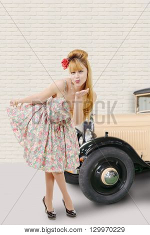 pretty pinup girl sending kisses vintage car background