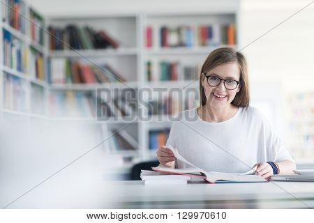female student study in  library using laptop and searching for informations on internet