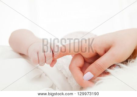 Newborn baby grasping her mother's finger. Concept of child care, feeling safe, parent love.