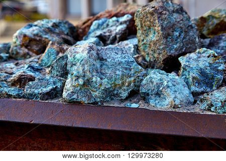 Chunks of copper ore mineral rocks in an iron barrel