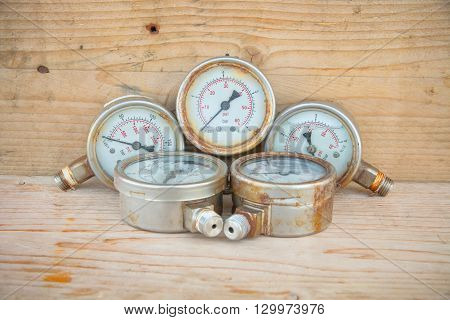 Old pressure gauge or damage pressure gauge of oil and gas industry on wooden background, Equipment of production process