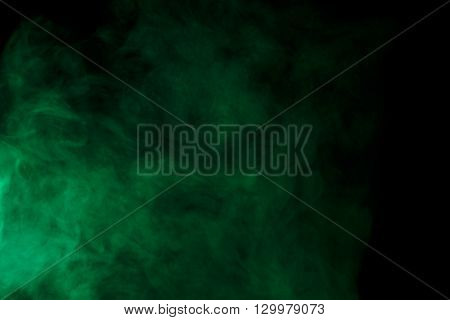 Abstract art. Green smoke hookah on a black background. Inhalation. The steam generator. The concept of poison gas. Gas.