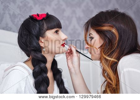 Makeup artist doing make-up the bride before the wedding. Morning of the bride. Cute makeup.