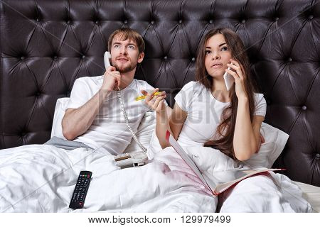 Morning business couple. Husband and wife on the phone. Family business. Viewing on TV Morning stock price.