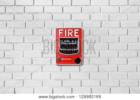 Fire alarm switch on white brick wall texture background