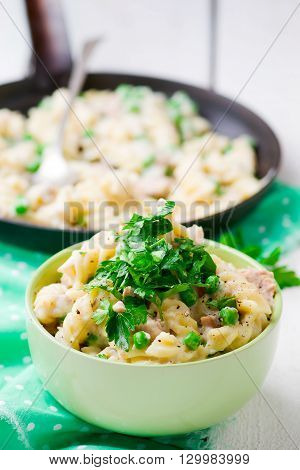 pasta with green peas tuna and creamy sauce. style vintage. selective focus.