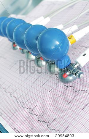 ECG electrodes on the printed graph. Unusual angle view poster