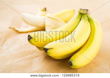 Fresh organic bananas on brown paper as background