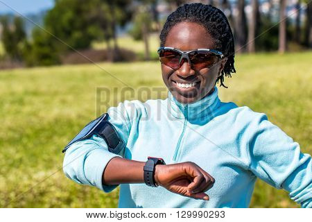 Close up portrait of young afro american woman in sportswear.Girl standing outdoors with smart phone and smart watch to track activity.
