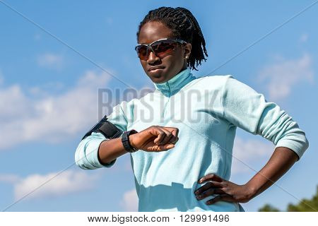 Close up outdoor portrait of young african girl reviewing results on smart watch.Woman in sportswear looking at smart watch against blue sky.