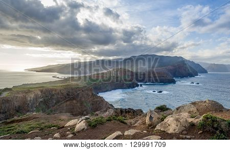 Panoramic landscape of the volcanic island. Warm evening sunlight, hills and mountains on the horizon. Madeira, Portugal.