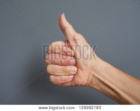 a hand making thumb up on gray background