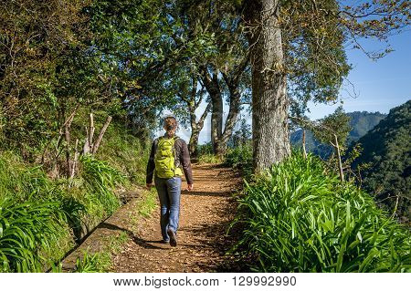 Woman with backpack is walking on Balcoes levada hiking route. Madeira island, Portugal.