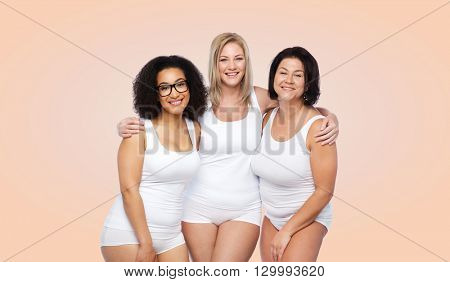 friendship, beauty, body positive and people concept - group of happy plus size women in white underwear over beige background