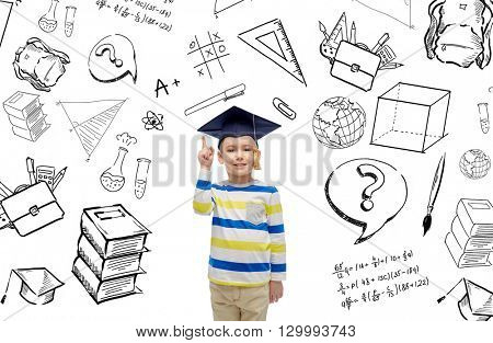 childhood, school, education, learning and people concept - happy boy in bachelor hat or mortarboard pointing finger up with doodles