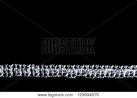 Minimalist abstract dark background with transparent glass particles. The texture.