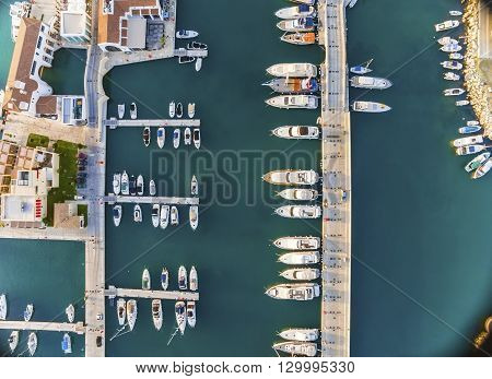 Aerial view of the beautiful Marina in Limassol city in Cyprus the boats lined up piers and commercial area from above. A very modern high end and newly developed space where yachts are moored and it's perfect for a waterfront promenade.