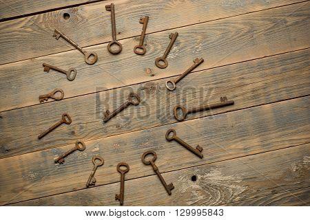 Antique copper keys on old wooden background.
