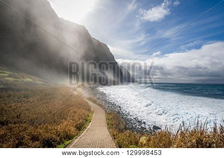 Dreamy landscape with walking path along the ocean shore, fields and high rocky mountains in the strong fog. Calhau das Achadas, Madeira island, Portugal.